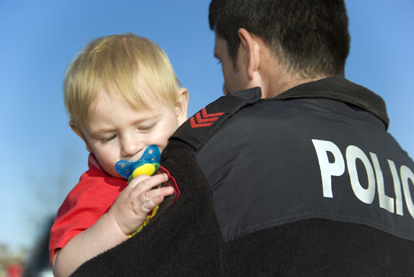 Police Officer protects and holds baby